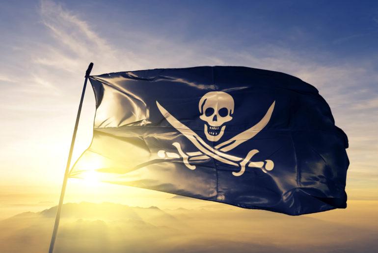 Pirate Flag flag on flagpole textile cloth fabric waving on the top sunrise mist fog